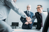 partial view of multiehtnic business colleagues shaking hands in office - 192093798