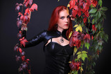 Blue Eyed Red Head Gothic Girl among colorful autumn vines