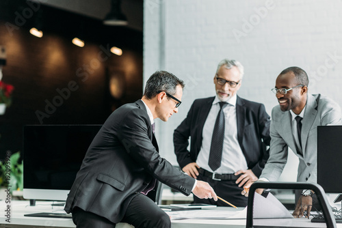 Fridge magnet multiethnic businessmen discussing new business strategy on meeting in office