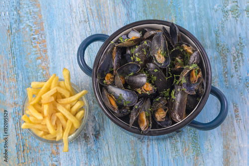 mussels in a blue ceramic pot on a blue wooden background. with a glass bowl of french fries. Meditteranean lifestyle.