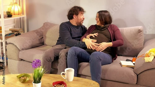 Man touching pregnant belly of wife sitting on couch feeling kick of baby