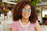 Cute African American female in trendy shades, has wavy dark hair, enjoys summer vacations, spends time at cafeteria, thinks where to go after dinner. Relaxed dark skinned woman being pleased - 192104188