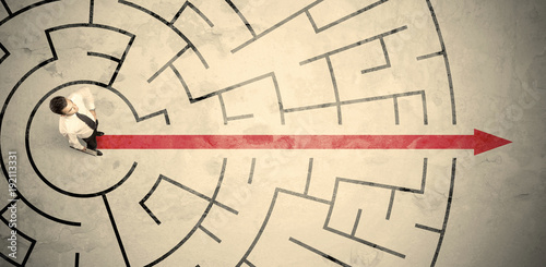 Business person standing in the middle of a circular maze - 192113331