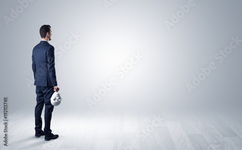 Man with object in his hand in an empty space