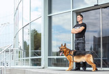 Security guard with dog near building - 192114354