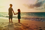 little boy and girl holding hands walk at sunset - 192120111