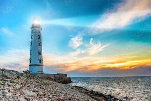 Fotobehang Vuurtoren Lighthouse searchlight beam through sea air at night. Seascape at sunset