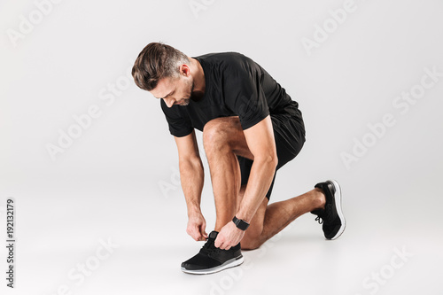 Fotobehang Hardlopen Portrait of a mature sportsman tying his shoelaces