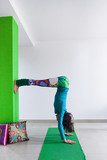 woman doing hand stand against wall indoor yoga class - 192133932