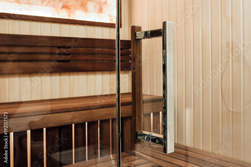 Handle clamp for the glass door to the sauna. On one side is a metal one, on the other hand a wooden look in the interior