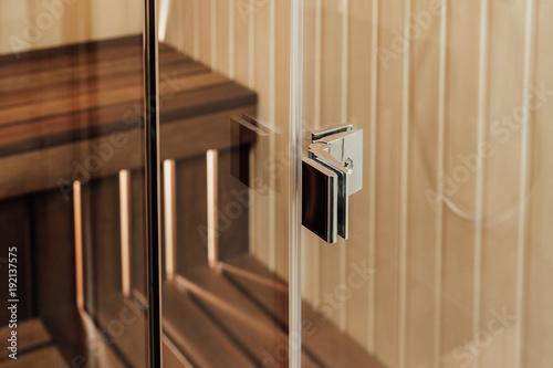 Metalowe zapięcia do szklanych ścian w saunie i kabinie prysznicowej we wnętrzu