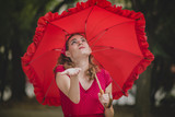 Young woman dressed in vintage red clothes holding an umbrella, checking for the rain - 192141591