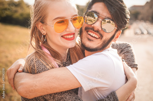 Pretty couple in sunglasses is hugging tight on the street.