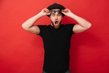 Portrait of surprised stylish man 30s in hat posing on camera and taking off black sunglasses, isolated over red background - 192145567