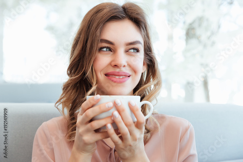 Papiers peints Cafe Portrait of a satisfied young woman holding cup of coffee