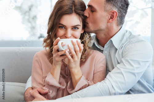 Elegant caring man hugging and kissing his beautiful young girlfriend in city cafe, while happy woman drinking tea or coffee