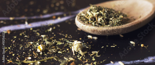 Herbal tea in a wooden spoon on a black marble background