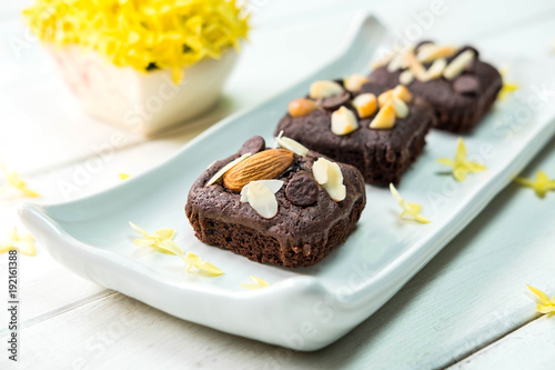 Foto op Canvas Chocolade Brownie cake with almond on top with yellow flower in the background
