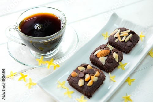 Papiers peints Cafe Chocolate brownie cake in white plate on old white table , there is hot coffee in white cup and beautiful yellow flower in the background