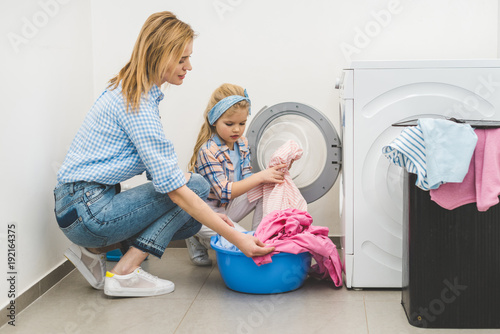 side view of mother and daughter putting laundry into washing machine at home