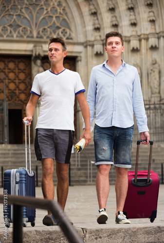 Men travelers with luggage heading to hotel on foot