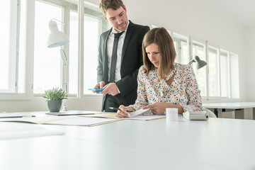 Female and male accountant calculating costs and expenses