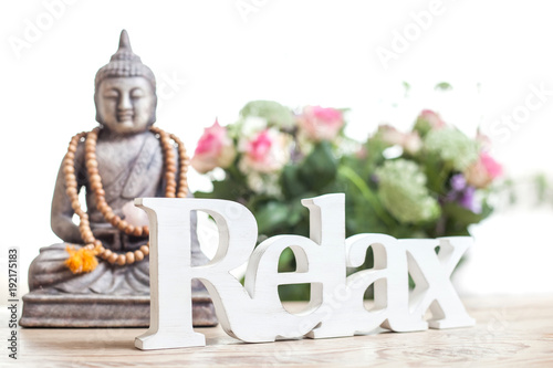 Fotobehang Boeddha Buddha statue with beads. Buddha statue and the word relax in wood lettering.