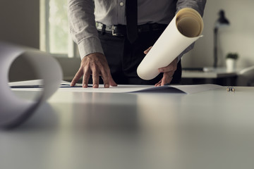 Businessman working on blueprints in an office in a low angle view