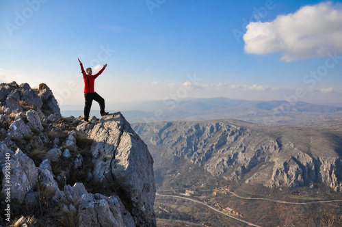 Young man on a cliff edge on the top of mountain with gorgeous view. Hiker on mountain peak on beautiful sunny day