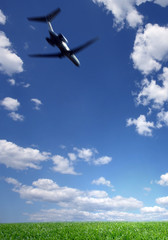 Airplane Flying in a Blue Sky over Green Grass