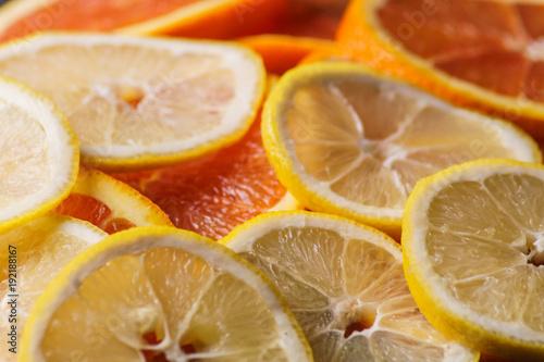 Fresh juicy orange and lemon fruit rings close up background.
