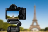 Camera on a tridop takes a picture of an Eiffel tower in Paris