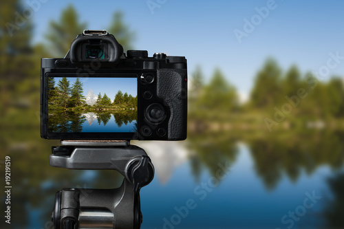 Camera on a tridop takes a picture of a mountain landscape