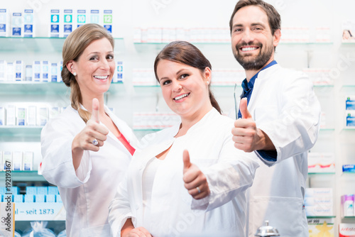Fotobehang Apotheek Pharmacists in pharmacy showing thumbs up and smiling