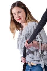 Junge Frau mit grauem Shirt und Jeans zieht an einem Seil