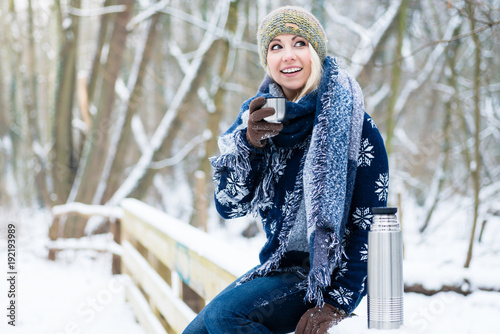 Woman freezing on a cold winter day warming herself up with hot drink in the snow