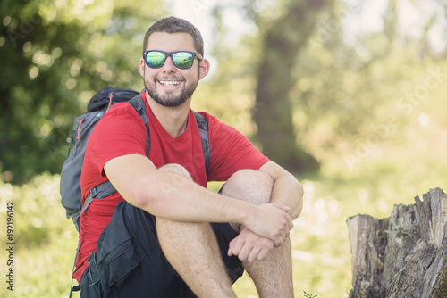 Happy young man with backpack hiking in the woods