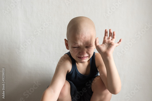 The child is upset because of problems in the family. Sits at the wall and protects himself with his hands.