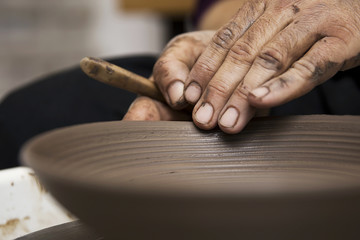 Artist makes clay pottery on a spin wheel