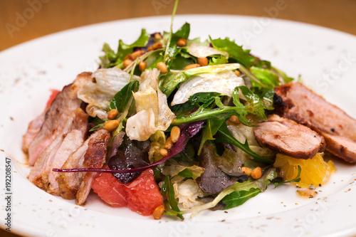 Restaurant dish meat salad from pork and arugula