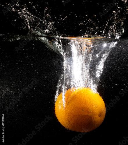 Orange under water on a black background