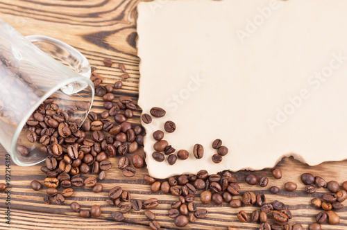 Papiers peints Café en grains Fried coffee beans poured out of glass beside burnt blank paper on old wooden rustic brown planks
