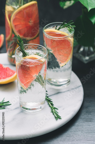 Cold detox cocktails with grapefruit and rosemary on a white marble serving tray.