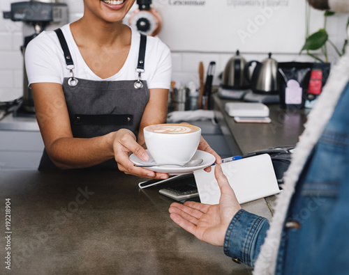 Fototapeta Unrecognizable coffee shop owner handing over a cup of coffee to her customer