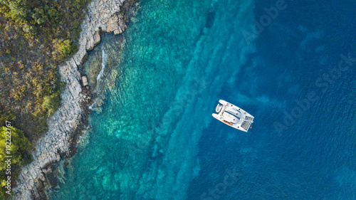 Foto op Plexiglas Tropical strand Aerial view of anchoring catamaran next to island.