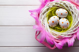 Easter eggs in the nest and pink basket on white wooden table - 192223507