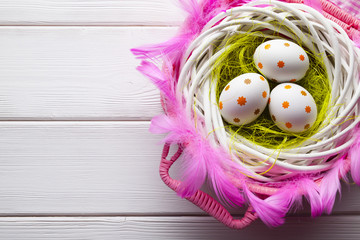 Easter eggs in the nest and pink basket on white wooden table