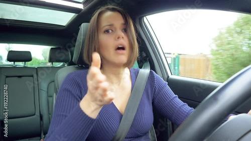 Woman driving angry looking camera talking unhappy
