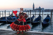 Wonderful costume in black and red with red heart in front of San Giorgio Maggiore, Venice, Carnival