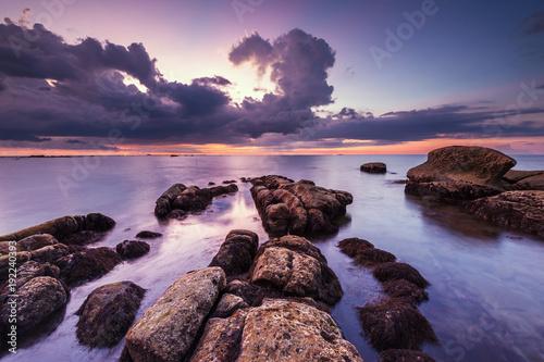 Aluminium Zee zonsondergang Sunset seascape with natural coastal rocks. Image contain soft focus due to long expose.